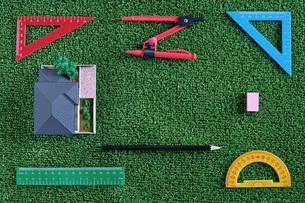 緑の人工芝に置いたミニチュアの家と定規などの文房具の写真素材 [FYI01222488]
