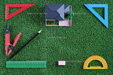 緑の人工芝に置いたミニチュアの家と定規などの文房具の写真素材 [FYI01222489]