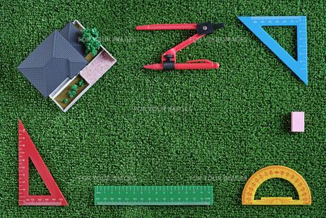 緑の人工芝に置いたミニチュアの家と定規などの文房具の写真素材 [FYI01222490]