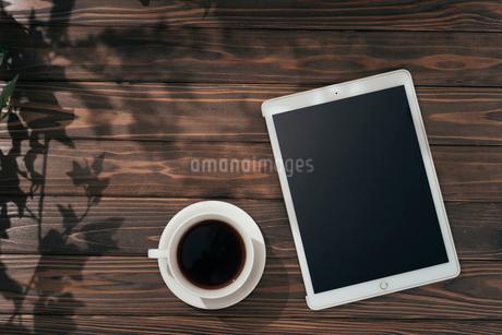 木目の机の上に置いてあるiPadとコーヒーカップの写真素材 [FYI01222517]