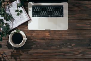 葉っぱの観葉植物と本とPCとコーヒーカップの写真素材 [FYI01222625]