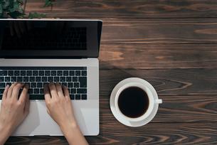 PCを触っている手とコーヒーカップの写真素材 [FYI01222638]