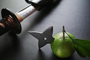 横位置の黒い板の上の手裏剣が刺さったミカンと日本刀の写真素材 [FYI01222756]