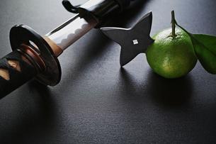 横位置の黒い板の上の手裏剣が刺さったミカンと日本刀の写真素材 [FYI01222757]