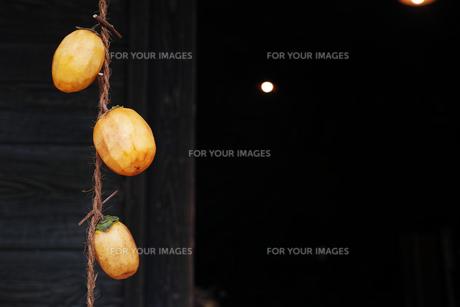 軒先に吊るした干し柿にする柿の写真素材 [FYI01223020]
