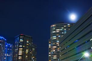 高層マンションと薄雲にぼんやり霞んだ満月の写真素材 [FYI01223025]