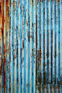 塗装が剥げた古い波鉄板のフェンスの写真素材 [FYI01223092]