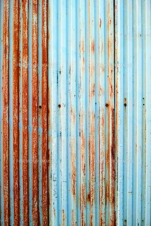 塗装が剥げた古い波鉄板のフェンスの写真素材 [FYI01223093]