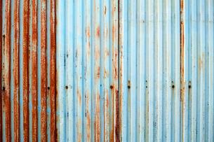 塗装が剥げた古い波鉄板のフェンスの写真素材 [FYI01223094]