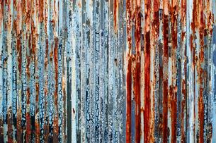 塗装が剥げた古い波鉄板のフェンスの写真素材 [FYI01223095]