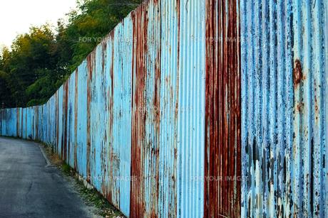 塗装が剥げた古い波鉄板のフェンスの写真素材 [FYI01223096]
