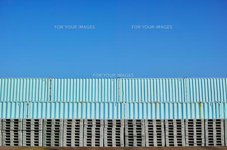 横位置の快晴の青空の下にパレットとコンテナが積まれている風景の写真素材 [FYI01223097]