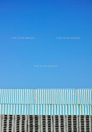 縦位置の快晴の青空の下にパレットとコンテナが積まれている風景の写真素材 [FYI01223098]