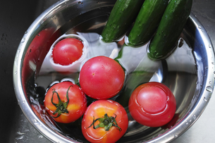 ステンレスのボウルの水に浸るトマトとキュウリの写真素材 [FYI01223473]