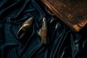 黒布の上に置かれた靴と旅行鞄の写真素材 [FYI01224007]