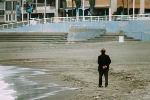 浜辺を歩く老人の写真素材 [FYI01224027]