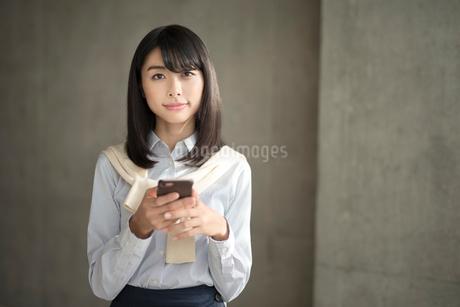 iPhoneを両手で持ってこちらを見ている20代OL女性の写真素材 [FYI01224951]