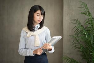 iPadを持って液晶を見つめる20代OL女性の写真素材 [FYI01224952]