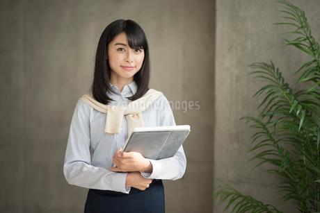 iPadを両手で抱える笑顔の20代OL女性の写真素材 [FYI01224955]