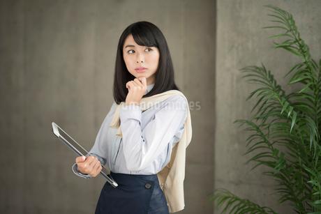 iPadを片手で持ち考え込む20代OL女性の写真素材 [FYI01224957]