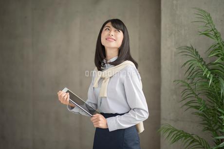 iPadを抱えて立つ笑顔の20代OL女性の写真素材 [FYI01224959]