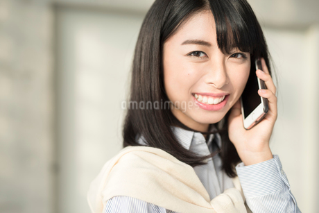 iPhoneで通話中の笑顔な20代OL女性。顔寄り。の写真素材 [FYI01225179]