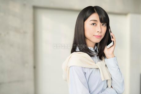 iPhoneで通話中の20代OL女性の写真素材 [FYI01225181]