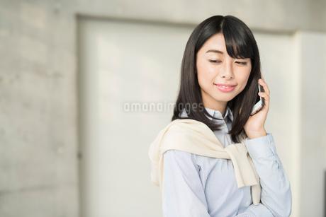 iPhoneで通話中の20代OL女性の写真素材 [FYI01225182]
