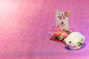 ピンクに輝く背景に年賀状カード用の可愛く微笑む一匹の白い猪のフィギャーと迎春と書いてある和紙の飾りの写真素材 [FYI01225832]
