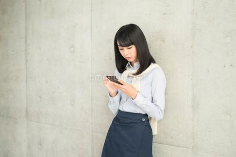 コンクリートの壁に寄りかかりながらiPhoneを見ている20代OL女性の写真素材 [FYI01226097]
