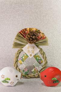 キラキラした銀色の背景に謹賀新年と書いてあるお正月の飾りと猪のフィギュアの写真素材 [FYI01226138]
