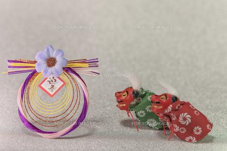 キラキラした銀色の背景に謹賀新年と書いてある藁制のお正月の飾りと獅子舞のフィギュアの写真素材 [FYI01226139]