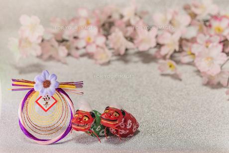 桜の花を背景に迎春と書いてあるお正月の飾りと獅子舞のフィギュアの写真素材 [FYI01226140]
