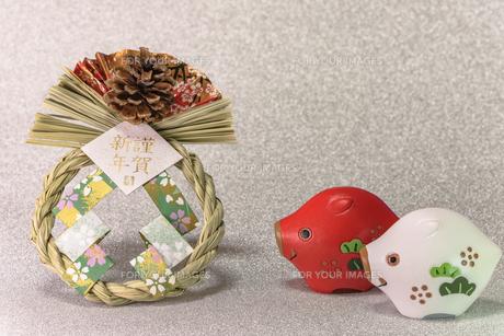 キラキラした銀色の背景に謹賀新年と書いてある藁制のお正月の飾りと猪のフィギュアの写真素材 [FYI01226142]
