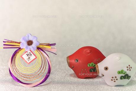 キラキラした銀色の背景に迎春と書いてあるお正月の飾りと猪のフィギュアの写真素材 [FYI01226144]