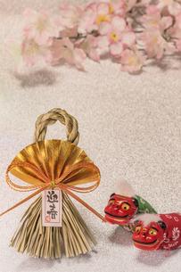 桜の花を背景に迎春と書いてある藁制のお正月の飾りと獅子舞のフィギュアの写真素材 [FYI01226145]
