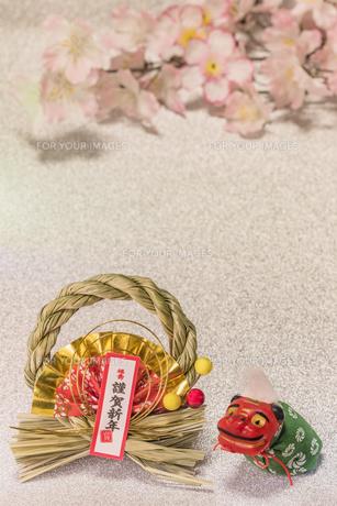 桜の花を背景に謹賀新年と書いてある竹と和紙制のお正月の飾りと獅子舞のフィギュアの写真素材 [FYI01226147]
