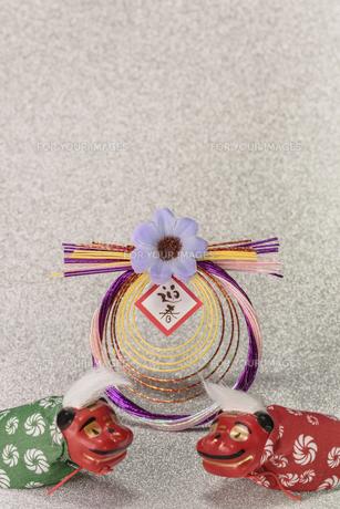 キラキラした銀色の背景に迎春と書いてあるお正月の飾りと獅子舞のフィギュアの写真素材 [FYI01226148]