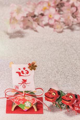 桜の花を背景に迎春と書いてある竹と和紙制のお正月の飾りと獅子舞のフィギュアの写真素材 [FYI01226149]