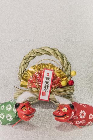キラキラした銀色の背景に謹賀新年と書いてある藁制のお正月の飾りと獅子舞のフィギュアの写真素材 [FYI01226150]