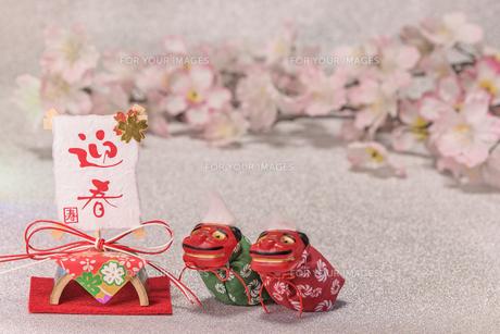 桜の花を背景に迎春と書いてある竹と和紙制のお正月の飾りと獅子舞のフィギュアの写真素材 [FYI01226151]