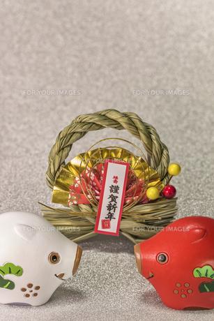 キラキラした銀色の背景に謹賀新年と書いてある藁制のお正月の飾りと猪のフィギュアの写真素材 [FYI01226152]