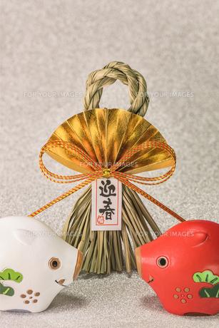 キラキラした銀色の背景に迎春と書いてある藁制のお正月の飾りと猪のフィギュアの写真素材 [FYI01226154]