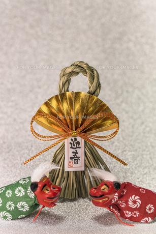 キラキラした銀色の背景に迎春と書いてある藁制のお正月の飾りと獅子舞のフィギュアの写真素材 [FYI01226156]
