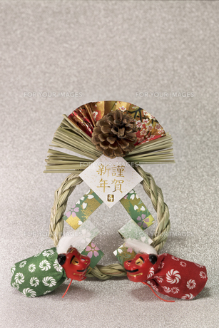 キラキラした銀色の背景に謹賀新年と書いてある藁制のお正月の飾りと獅子舞のフィギュアの写真素材 [FYI01226158]