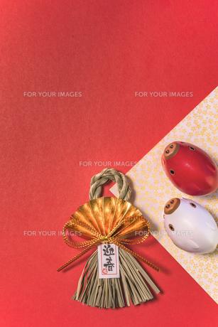 キラキラした銀色の背景に迎春と書いてある藁制のお正月の飾りと猪のフィギュアの写真素材 [FYI01226176]