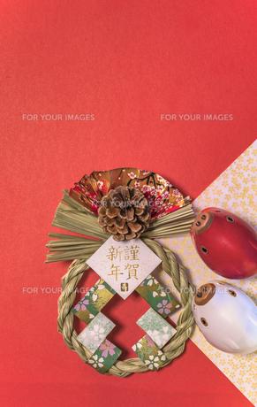 赤い背景に謹賀新年と書いてある藁制のお正月の飾りと猪のフィギュアの写真素材 [FYI01226178]