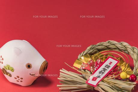 赤い背景に謹賀新年と書いてある藁制のお正月の飾りと猪のフィギュアの写真素材 [FYI01226180]