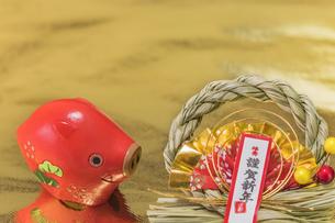 金箔の背景に謹賀新年と書いてある藁制のお正月の飾りと猪のフィギュアの写真素材 [FYI01226182]