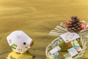 金箔の背景に謹賀新年と書いてある藁制のお正月の飾りと猪のフィギュアの写真素材 [FYI01226184]